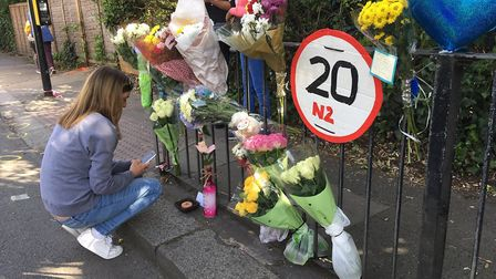 An onlooker observes the flowers left on East End Road, East Finchley, where a toddler was killed la