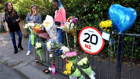 Neighbours bring flowers to the scene of the accident at the pedestrian crossing on East End Rd in