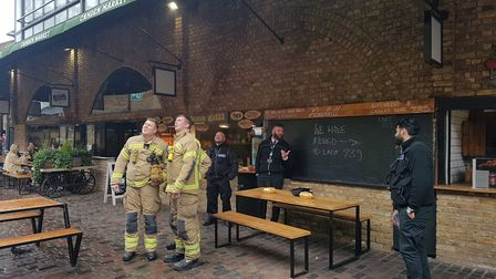 Bemused firefighters spot a stranded squirrel at Camden Stables Market. Picture: David Cole