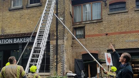 Firefighters consider rescuing a squirrel at Camden Stables Market. Picture: David Cole