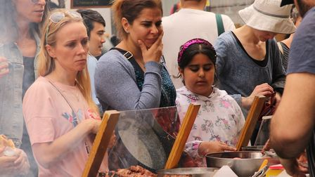 Visitors eye up the offerings from the Greek food stall. Picture: Shanei Stephenson-Harris