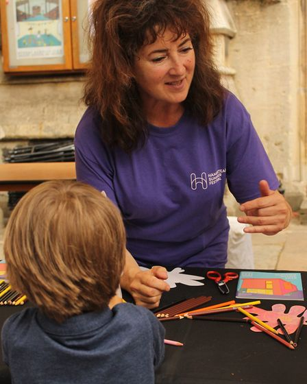 An organiser from the Hampstead Summer Festival helps children with their artwork. Picture: Shanei S