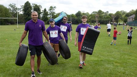 Jonathan Joseph and club members move equipment during the NatWest RugbyForce Weekend at Hackney RFC
