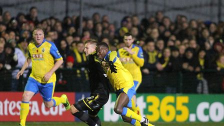 Rakim Richards of Haringey Borough and AFC Wimbledon's Joe Pigott battle for the ball in the first r