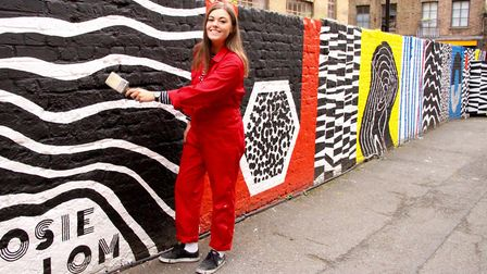 Rosie Lom next to her mural