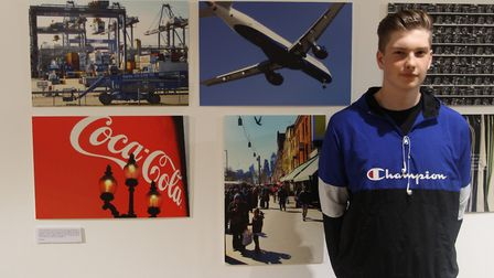 Alex Clarke with his photographs at the exhibiton. Picture: Guy Holden