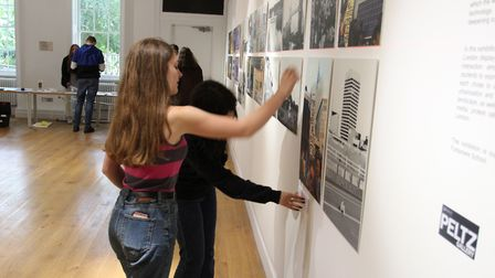 Two photography students examine their work before the public are allowed into the gallery to see it