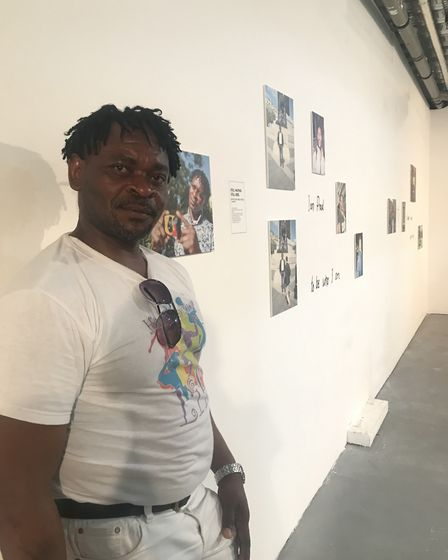 Roger Lemoumbou Fokou, who started photography two months ago, standing next to some of the photos h