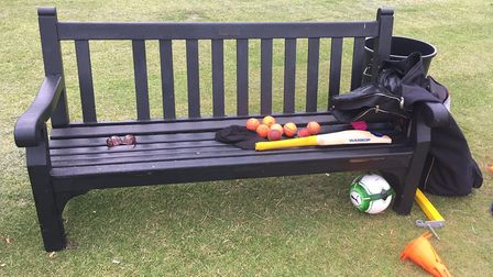 Cricket equipment is left on a bench
