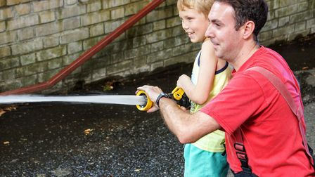 A firefighter helps a youngster use the fire house from his fire truck at last year's Queen's Cresce