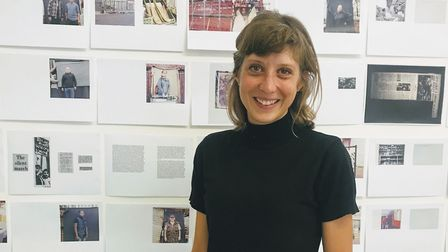 Tamara Stoll in front of a wall of pages from her book.