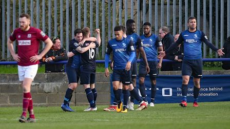 Charlie Ruff of Wingate & Finchley scores the fourth goal for his team and celebrates with his team