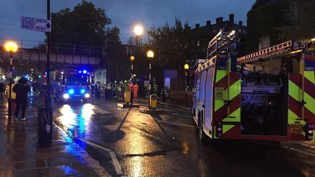 Emergency services in Highgate Road in Kentish Town after a man fell onto train tracks below.