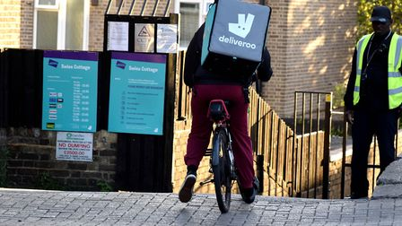 A cyclist with a Deliveroo ruck sack on enters the Swiss Cottage editions kitchen. Picture: Polly Ha