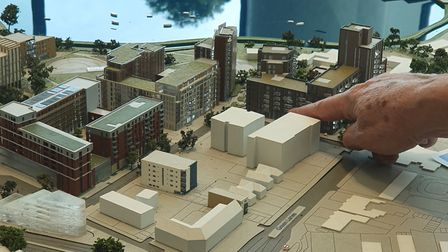 A resident points Nathaniel Court on a scale model of the regeneration project.