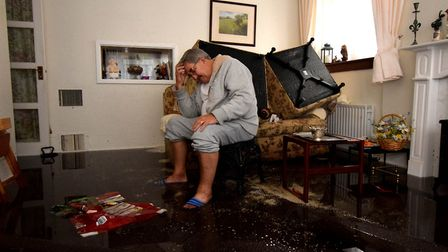 Brian Bicknell looks at the debris in the living room of the ground floor flat he shares with his wi