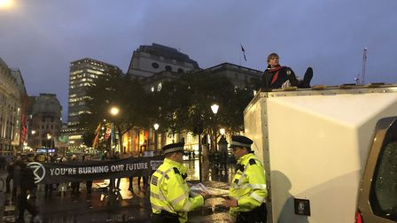 Police guard a trailer which an Extinction Rebellion protestor has glued themselves to the top of. P