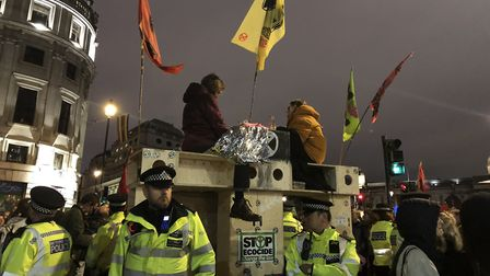 Extinction Rebellion protestors glue themselves to the top of a wooden structure in Trafalgar Square