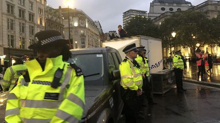 Extinction Rebellion protestors block Trafalgar Square with a car and trailer. Two people who locked