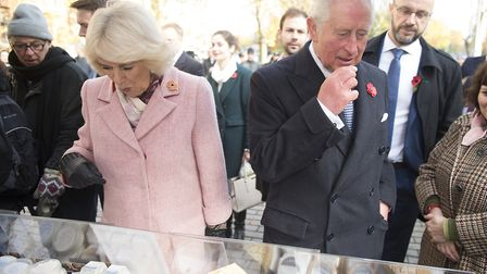 The Prince of Wales and Duchess of Cornwall browse a cheese stall during a visit to Swiss Cottage Fa