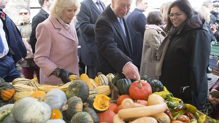 The Prince of Wales and Duchess of Cornwall look at an array of vegetables during a visit to Swiss C