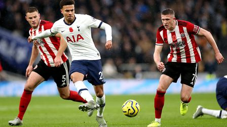 Tottenham Hotspur's Dele Alli (centre) battles for the ball with Sheffield United's Jack O'Connell (