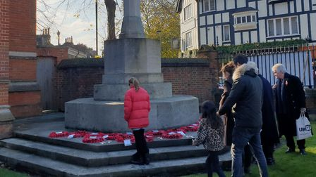 A group stops to look at the wreaths laid on the war memorial at Highgate School. Picture: Harry Tay