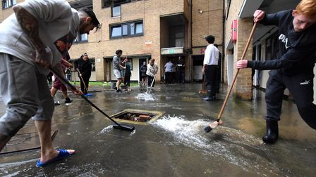 Residents clean up the flood water on the Kings Crescent Estate. Picture: POLLY HANCOCK