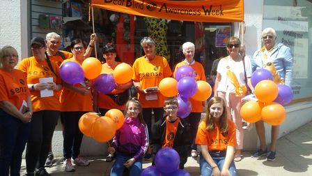 A charity walk took place in Lowestoft for Deafblind Awareness Week. Walkers stand outside the Sense
