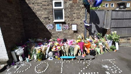 Photographs and flower tributes form a homemade shrine for Tashaun Aird on the Somerford Grove Estat