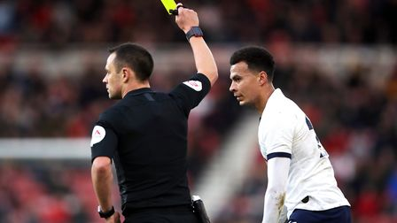 Tottenham Hotspur's Dele Alli is shown a yellow card by referee Stuart Attwell during the FA Cup thi