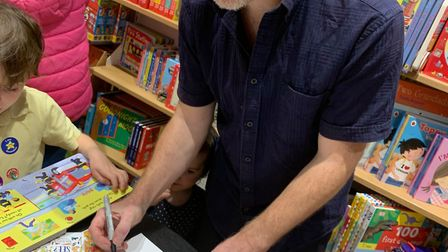 Jason Korsner signs copies of his books What Can You See and I Like To Put Food in My Welly
