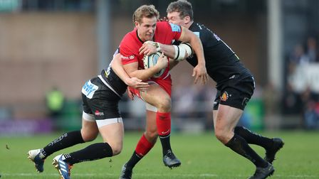 Saracens' Max Malins is tackled by Exeter's Joe Simmonds and Ian Whitten