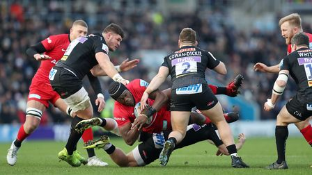 Saracens' Maro Itoje is tackled by Exeter's Sam Simmonds and Luke Cowan-Dickie