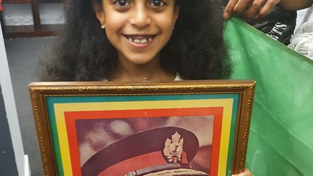 Young girl holds a picture of Haile Selassie - the last emperor and former leader of Ethiopia. He re