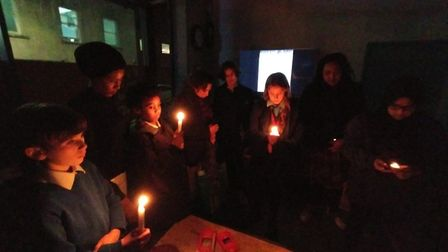 Children and adults stand together at a candlelit vigil to observe a one minute silence. Picture: Av