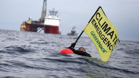 "Greenpeace campaigner Sarah North holds a banner reading ""Climate Emergency"" whilst floating in fron"