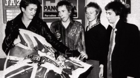 The Sex Pistols tearing an EMI poster after the announcement that they have split with their record
