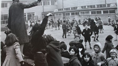 A Gospel Oak teacher rings the bell to bring an end to playtime. Picture: Henry Grant