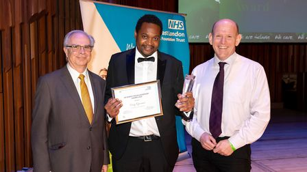 Day Njovana (centre) receiving his award from Philip Turner of Luton Healthwatch and ELFT deputy CEO