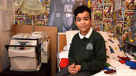 Tyshan, 13, in his bedroom with his dialysis machine and supplies next to the bed. Picture: Polly Ha