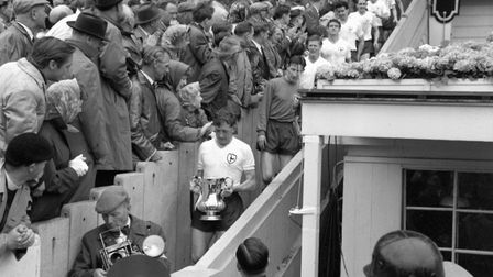 Tottenham captain Danny Blanchflower, holding the FA Cup, leads his men past fans on the way down fr
