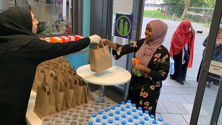 Careful queuing to pick up food at the Queens Crescent Community Association's 'Takeaway Iftar'. Pic