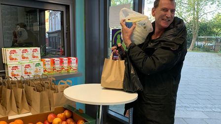 A man carefully picks up food at the Queens Crescent Community Association. Picture: QCCA