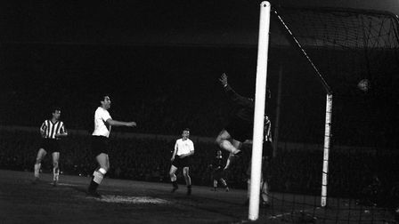 Sheffield Wednesday and England goalkeeper Ron Springett (partly obscured by post) leaps high in an