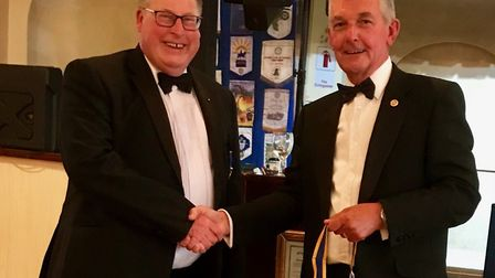 The outgoing president of Lowestoft East Point Rotary Club, Paul Tabiner, hands over the chain of of