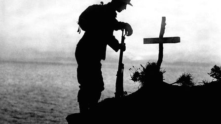 File photo dated 01/11/1915 of a British soldier paying his respects at the grave of a colleague nea