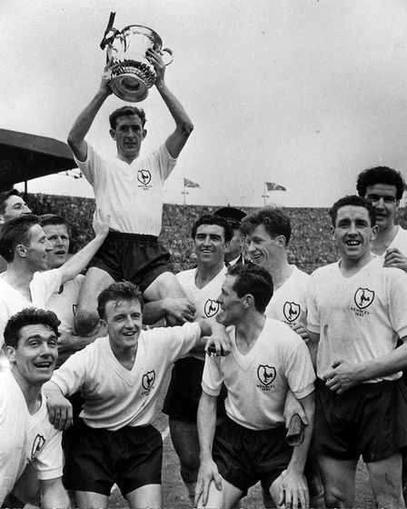Tottenham Hotspur Captain Danny Blanchflower holds the FA Cup as he is carried by his team-mates aft