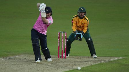 Middlesex batsman Eoin Morgan drives watched by Nottinghamshire Outlaws wicketkeeper Tom Moores duri