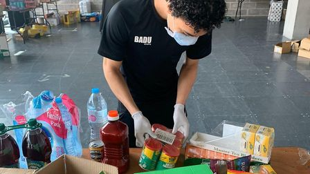 A young volunteer helps out at the food bank at Olympic Park's Here East. Picture: Badu